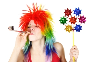 young beauty woman in multicolored clown wig with party blower a